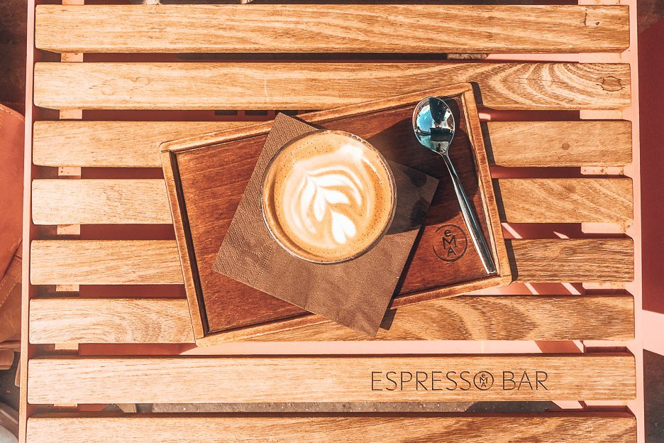 A latte on a wooden seat at EMA Espresso Bar, Prague,