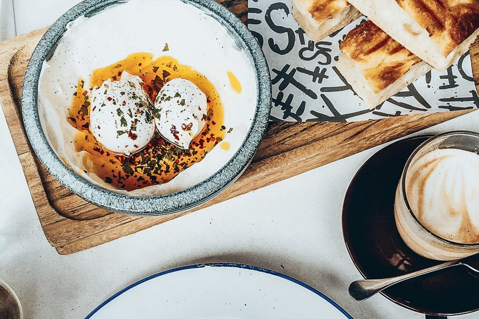 Poached eggs with chilli oil, pitta bread and coffee - Brunch in London