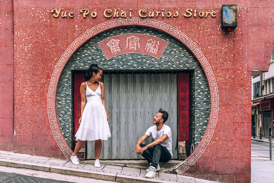 a couple pose in the circular archway of Yue Po Chai Curios Store, Hong Kong