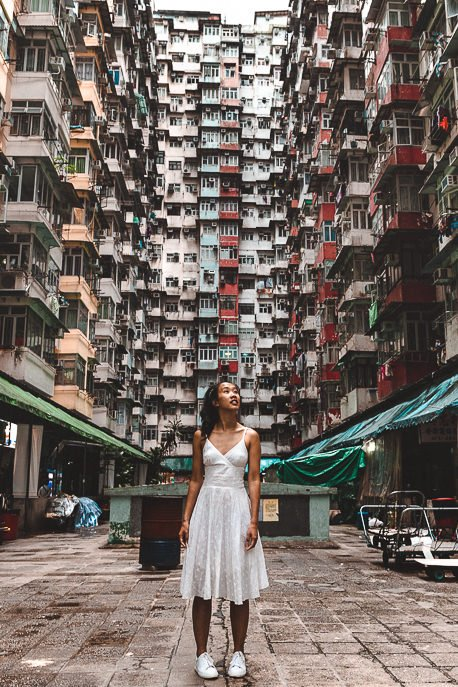 A girl stands in the courtyard of Yick Fat Building Hong Kong