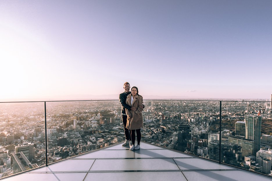 A couple pose at the edge of Shibuya Sky Observation Deck at sunset | Shibuya what to do