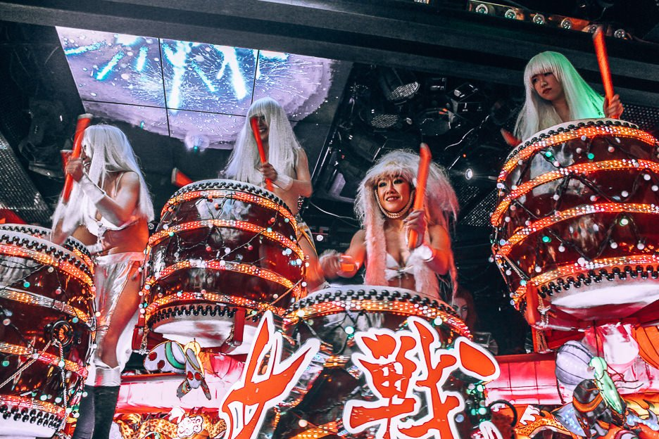 Four ladies in long white wigs bang drums at the Robot Restaurant | Shinjuku what to see