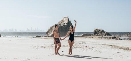 A couple walk hand in hand along Currumbin Beach, Gold Coast Australia